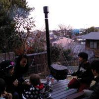 薪ストーブを囲んで談笑する人たち