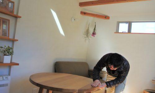 楢ダイニングテーブルにヤスリをかける人