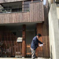 杉板の外壁とお清めしている人